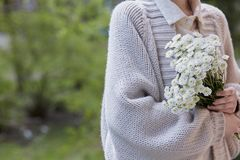 Photo of young woman holding white flowers with green stem in her hands. Close up photo of young woman wearing grey cardigan, white shirt, holding white flowers stock image