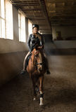 Photo of young woman jockey riding horse on manege Royalty Free Stock Photos