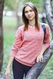 Photo of young woman in pink jacket on walk. At spring park during day Royalty Free Stock Image