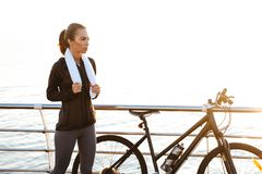 Photo of young woman with towel over neck standing near bicycle outdoors, after workout by ocean stock image