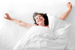 Photo of a young woman waking up happy Royalty Free Stock Images