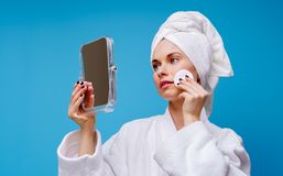 Photo of young woman in white coat and towel on her head with cotton pad and mirror in her hand. On empty blue background stock photography