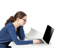 Photo of young woman working on laptop behind desk. Isolated on white photo of young woman working on laptop behind desk Stock Image