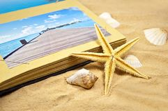Photoalbum med souvenir och skal med sand arkivbild