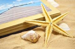 Photoalbum med souvenir och skal med sand royaltyfria foton