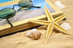 Photoalbum mit Andenken und Oberteilen mit Sand stockbild
