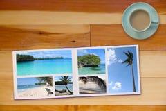 Photobook-Album auf Bretterboden-Tabelle mit Reise-Fotos und Kaffee oder Tee in der Schale Stockbilder