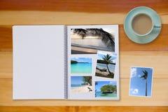 Photobook-Album mit Reise-Foto auf Bretterboden-Tabelle mit Kaffee oder Tee in der Schale Stockbild