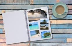 Photobook-Album mit Reise-Foto auf Bretterboden-Tabelle mit Kaffee oder Tee in der Schale Lizenzfreie Stockfotos