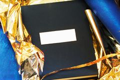 A photobook with a cover of a blue takani in a gift gold wrapper. stock images