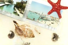Photobooken, cockleshellsna och sjöstjärnan är på sand Arkivfoton