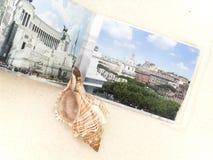 Photobooken och den stora cockleshellen är på vit sand Royaltyfria Bilder