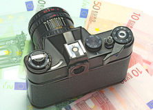 Photocamera lying on the euros. For background Stock Image