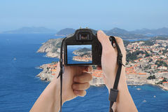 Photocamera in male hands taking picture of beautiful landscape Royalty Free Stock Images