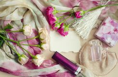 Photocomposition in a gentle vintage style in pastel colors. Tea pink roses lie on a silk scarf, surrounded by pearls, lipstick, p Stock Images