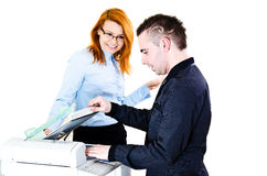 Photocopier flirting. Young office workers doing copies on photocopier and flirting Stock Photo