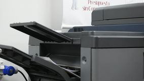 Photocopier machine running, pulling sheets to tray