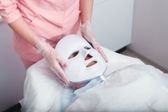 Photodynamic face mask therapy. Woman in the light photodynamic mask lying on a couch in a beauty salon. Pdt Stock Image