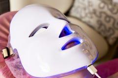 Photodynamic therapy facial mask on woman`s face. stock photos
