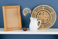 Photoframe和花瓶有一朵花的在白色架子在蓝色wallpa 免版税库存照片