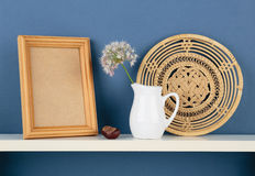 Photoframe和花瓶有一朵花的在白色架子在蓝色wallpa 免版税库存图片