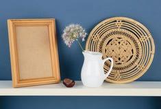 Photoframe和花瓶有一朵花的在白色架子在蓝色wallpa 库存照片