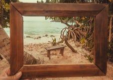 Photoframe για τη μνήμη για την ωκεάνια τροπική παραλία Ξύλινο banch κάτω από τους φοίνικες στο θερμό κόλπο κυμάτων Στοκ Εικόνες