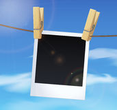 Photoframe on blue sky background, white clouds and clothes pins Stock Image