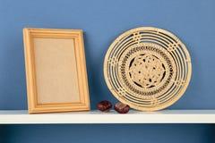 Photoframe com a cesta na prateleira branca no papel de parede azul Imagem de Stock