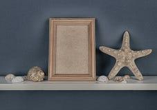 Photoframe com a estrela do mar na prateleira Fotografia de Stock Royalty Free