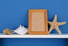 Photoframe com a estrela do mar na prateleira branca no papel de parede azul Fotografia de Stock