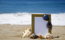 Photoframe on sandy beach. Photoframe with seashells and sunglasses on sandy beach Royalty Free Stock Photo