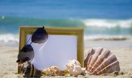 Photoframe on sandy beach. Photoframe with seashells and sunglasses on sandy beach Stock Photo