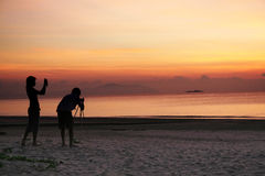 Photogaphing the sunrise. Photo enthusiasts capturing the sunrise on the beach Stock Image