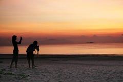 Photogaphing the sunrise. Photo enthusiasts capturing the sunrise on the beach stock image