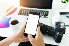 Photogeapher creativo que sostiene la pantalla blanca del teléfono en espacio de trabajo imagen de archivo