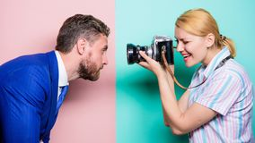 He is photogenic. Pretty woman using professional camera. Businessman posing in front of female photographer. He is photogenic. Pretty women using professional stock photos