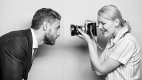 He is photogenic. Pretty woman using professional camera. Businessman posing in front of female photographer stock photography