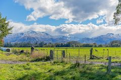 PHOTOGERAPHERS CAPTURING SNOW CAPPED MOUNTAINS AND LUSH MEADOWS NEAR CHRISTCHURCH. CHRISTCHURCH, NEW ZEALAND - April 2018: The snow capped alpine mountains and royalty free stock photos