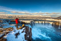 Photoghaper som tar ett foto på den Godafoss vattenfallet i vinter, Island arkivbilder