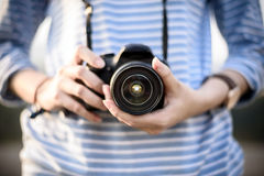 Photograher girl holds camera in garden Royalty Free Stock Images