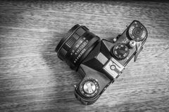 The photograph between art and the profession. An analog camera with 58mm lens on a wood texture. Grayscale photography Royalty Free Stock Photography