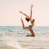 Photograph of a beautiful female dancer jumping  on a beach in t. He waves of the sea. Woohoo. Enjoy life.  Room for text Royalty Free Stock Images