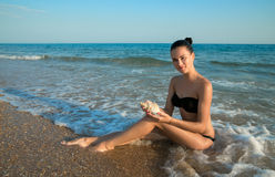 Photograph of beautiful model with big seashell in hands relaxin Royalty Free Stock Photo