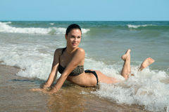 Photograph of a beautiful model relaxing on a beach in the waves Royalty Free Stock Photography