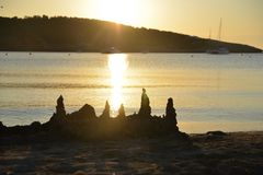 A beautiful sunset on the ocean with a sandcastle in the foreground. stock photos