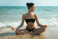 Photograph of a beautiful woman relaxing and meditating on a bea Royalty Free Stock Image