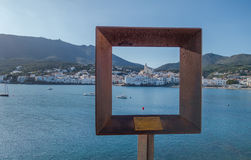 Cadaqués view in a frame. Photograph of Cadaqués in a steel frame in a sunny day, Cadaqués, Catalonia, Spain Stock Image