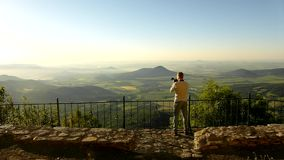 Photograph with camera in action within early morning on view point. Hills sticking out from flat landscape, stock footage