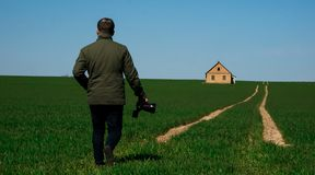 Photograph with a camera in hand walking down the road royalty free stock photo